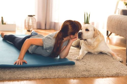 Ways to motivate yourself to work out today - girl on exercise mat next to dog