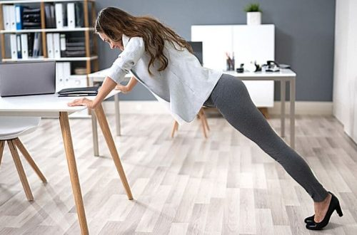 How to Stay Active When Working from Home - Woman doing incline pushups using her desk.