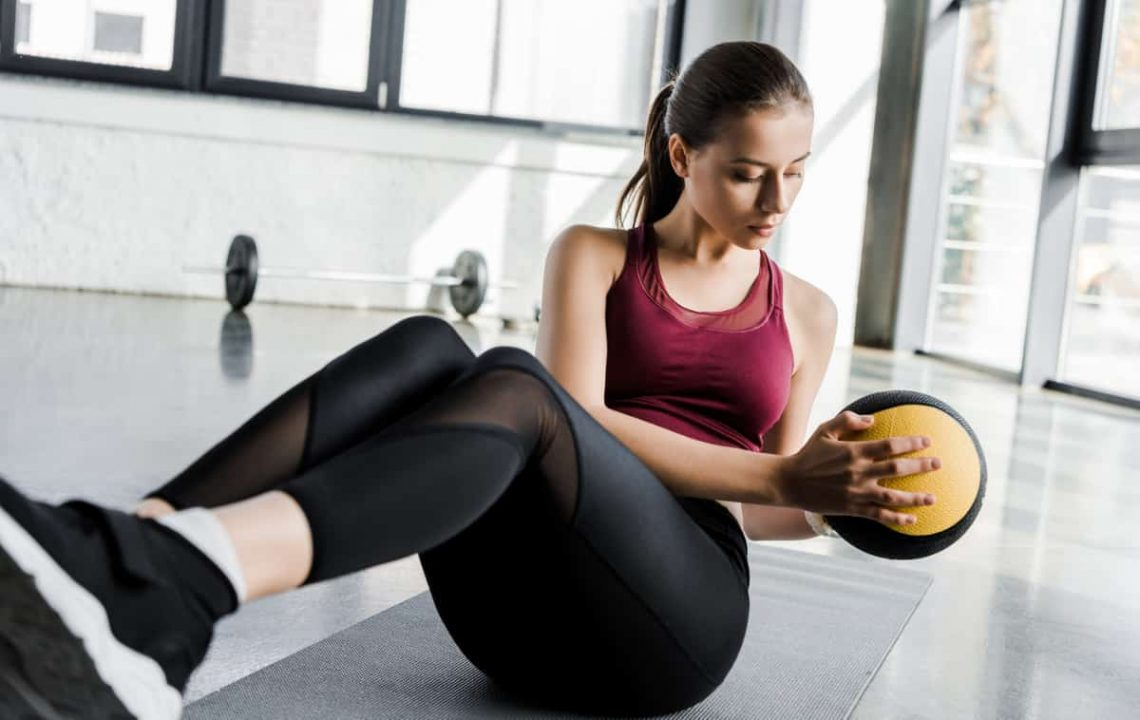 how to burn 1000 calories a day - woman doing russian twists with medicine ball